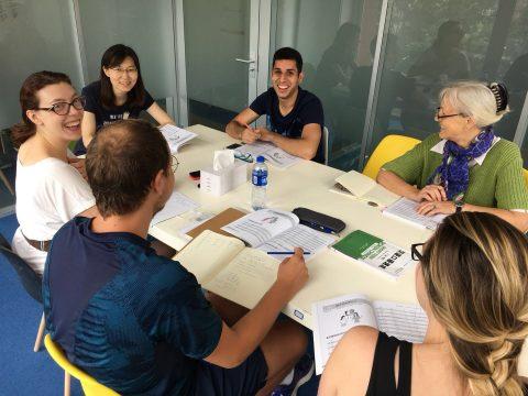 Fem elever lærere kinesisk i klasserom sammen med lærer i Shanghai