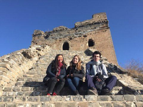 Elevene Jocelyn, Katrin and Nicolas sitter på den kinesiske muren