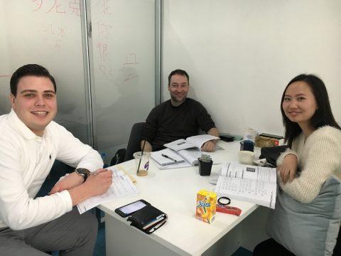 Henri sammen med en klassekamerat og lærer i klasserommet i Shanghai